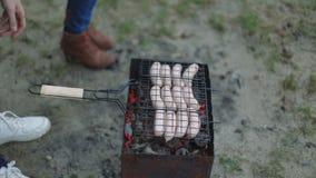 烤在热的格栅,人轮的变褐的香肠并且投入在火盆特写镜头 股票录像