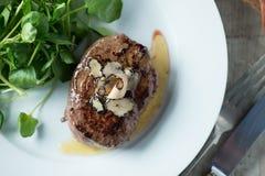 烤在白色盘的牛排用块菌和绿色 库存图片