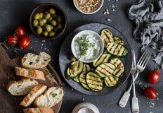 烤夏南瓜、橄榄、蕃茄、ciabatta -简单的快餐或开胃菜 地中海样式食物 在黑暗的背景,顶视图 免版税图库摄影
