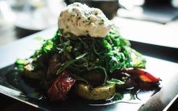 烤夏南瓜、蘑菇、甜椒与新鲜的芝麻菜和山羊乳干酪沙拉  免版税图库摄影