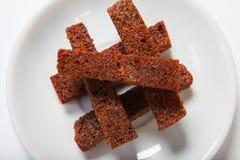 烤大蒜油煎方型小面包片,在一块白色板材的黑面包 免版税库存照片
