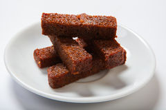 烤大蒜油煎方型小面包片,在一块白色板材的黑面包 库存照片