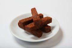 烤大蒜油煎方型小面包片,在一块白色板材的黑面包 免版税库存图片
