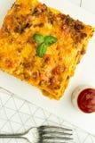 烤宽面条用剁碎的牛肉、博洛涅塞调味汁和蓬蒿在黑暗的板材 免版税库存图片
