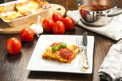 烤宽面条的开胃部分在一块白色板材的用西红柿酱 库存照片