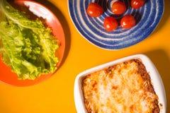 烤宽面条,蕃茄,在黄色背景的蔬菜沙拉 免版税库存图片