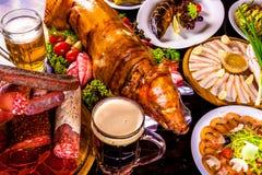 烤小猪、烤鱼、冷煮沸的猪肉、啤酒和开胃菜 图库摄影