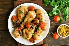 烤小鸡腿和烤蕃茄 库存照片