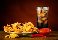 烤干酪辣味玉米片、辣调味汁垂度和可乐饮料 库存照片