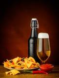 烤干酪辣味玉米片、辣调味汁垂度和啤酒 库存照片