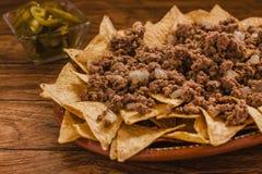 烤干酪辣味玉米片在墨西哥切削玉米装饰用绞细牛肉,熔化乳酪,在板材的墨西哥胡椒胡椒在木桌墨西哥辣食物 免版税库存照片