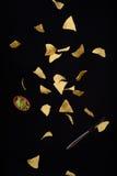 烤干酪辣味玉米片玉米粉薄烙饼与新鲜的鳄梨调味酱捣碎的鳄梨酱的玉米片调味飞行,黑背景 库存图片