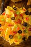 烤干酪辣味玉米片用乳酪、橄榄和辣椒 免版税库存照片