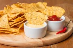 烤干酪辣味玉米片用各种各样的调味汁 免版税库存照片