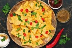 烤干酪辣味玉米片 玉米片特写镜头以调味汁、辣椒和绿色品种在黑暗的背景 从上面,地方fo的看法 免版税库存图片