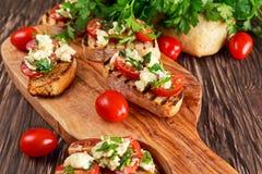 烤开胃菜bruschettas用蕃茄、无盐干酪和荷兰芹洒 免版税库存图片