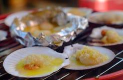 烤扇贝冠上了用在一个烤架的黄油在火 免版税图库摄影