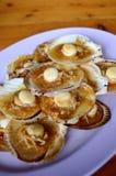 烤扇贝冠上了用黄油、大蒜和葱 图库摄影