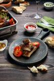 烤排骨和香肠供食用蕃茄和调味汁在木桌上 免版税图库摄影
