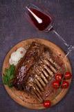 烤放在架子上的羊羔在香醋和红糖调味汁、玻璃和瓶的酒 与菜的羊排 免版税库存图片