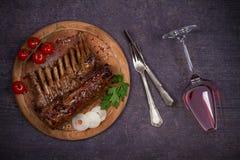 烤放在架子上的羊羔在香醋和红糖调味汁、玻璃和瓶的酒 与菜的羊排 免版税图库摄影