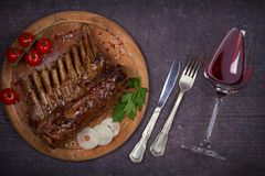 烤放在架子上的羊羔在香醋和红糖调味汁、玻璃和瓶的酒 与菜的羊排 库存照片