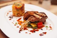 烤放在架子上的羊羔用土豆和菜 免版税库存照片