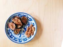 烤新鲜的无花果和杏仁在蓝色和白色板材 免版税库存照片