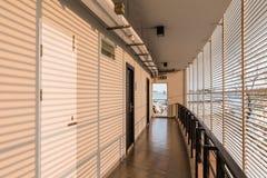 烤有在旅馆走廊白色墙壁上的被投下的阴影在清迈,泰国的橙色光的墙壁 免版税图库摄影