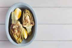 烤朝鲜蓟和柠檬在板材 背景空白木 这个产品有一最高的抗氧剂 免版税图库摄影
