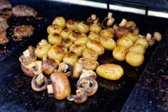 烤未张开的蘑菇和整个土豆在室外格栅 免版税库存照片