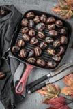 烤栗子在一张老桌上的栗子平底锅服务 库存照片