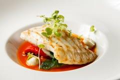 烤比目鱼、tabouli、甜椒调味汁和夏天菜 白色盘 免版税库存照片