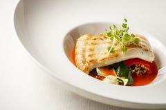 烤比目鱼、tabouli、甜椒调味汁和夏天菜 白色盘 免版税库存图片