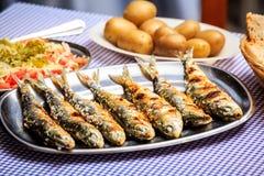 烤沙丁鱼用沙拉、面包和土豆 免版税库存照片