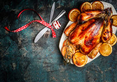 烤火鸡或鸡与橙色切片在板材圣诞晚餐的服务与叉子、刀子和欢乐装饰在黑暗的r 免版税库存照片