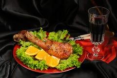 烤火鸡鼓槌用桔子、莴苣和红葡萄酒在bl 图库摄影