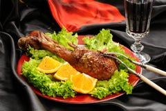 烤火鸡鼓槌用桔子和莴苣在黑和再 免版税库存图片