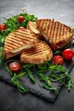 烤烟肉,乳酪三明治和服务在有芝麻菜和蕃茄的石盛肉盘 库存图片