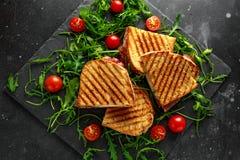烤烟肉,乳酪三明治和服务在有芝麻菜和蕃茄的石盛肉盘 免版税库存照片