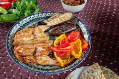 烤烟草鸡用在一块石板材的调味汁有保加利亚语的油煎了红辣椒茄子夏南瓜和大蒜 可口正餐 免版税图库摄影