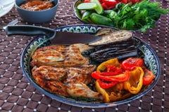 烤烟草鸡用在一块石板材的调味汁有保加利亚语的油煎了红辣椒茄子夏南瓜和大蒜 可口正餐 图库摄影