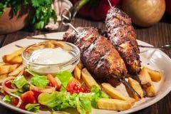 烤烤肉串服务与油煎的芯片和沙拉 库存照片