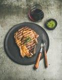 烤热的肋骨眼睛牛排用在玻璃的红葡萄酒 库存照片