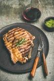 烤热的肋骨眼睛牛排用红葡萄酒 免版税图库摄影