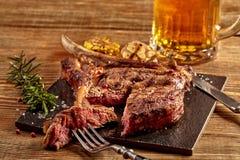 烤牛仔牛排、杯啤酒,草本和香料在木背景 顶视图 免版税图库摄影