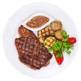 烤牛排、被烘烤的土豆和菜在白色板材  库存照片