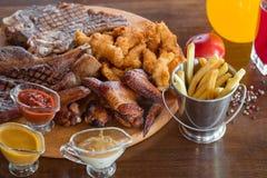 烤牛排、鸡翼和被分类的肉用炸薯条和调味汁在切口 顶视图 库存图片