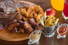 烤牛排、鸡翼和被分类的肉用炸薯条和调味汁在切口 顶视图 免版税图库摄影