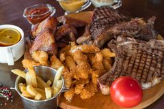 烤牛排、鸡翼和面包鸡黏附用炸薯条和调味汁在切口 顶视图 图库摄影